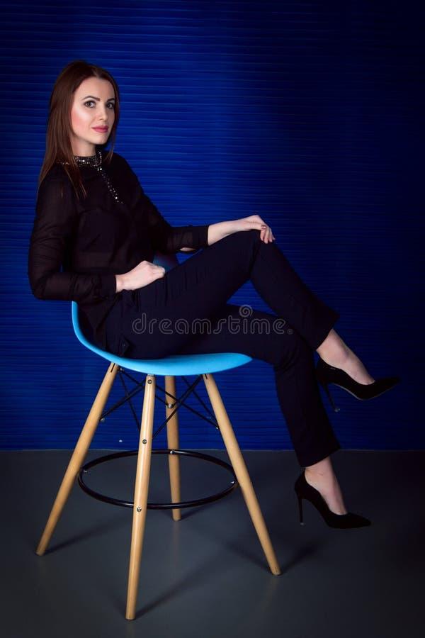 Stående av härligt ungt brunettkvinnasammanträde på stolen arkivfoto