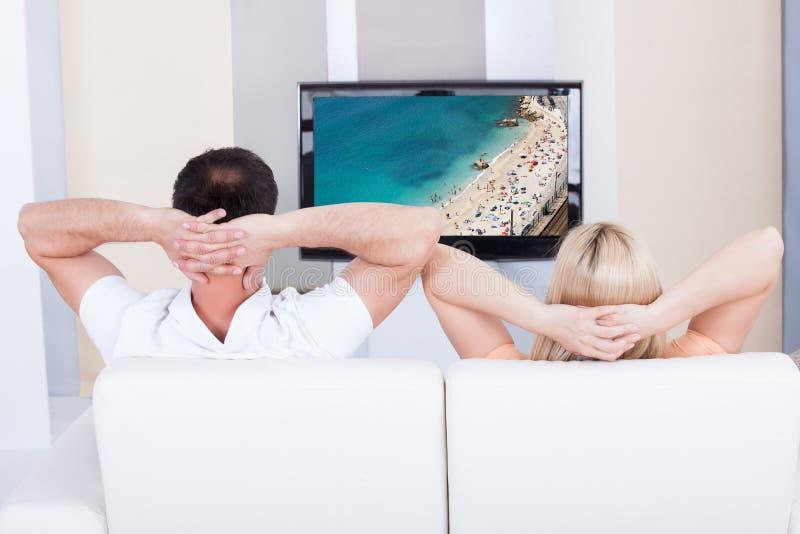 Stående av hållande ögonen på television för par royaltyfri foto