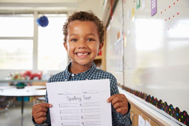 Stående av hållande övre för grundskolapojke hans provpapper arkivbild