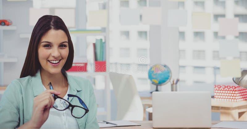 Stående av hållande glasögon för affärskvinna med bärbara datorn på kontoret arkivfoto
