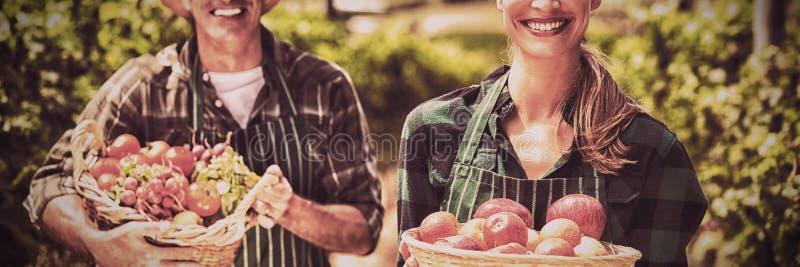 Stående av hållande korgar för lyckliga bondepar av grönsaker och frukter arkivfoton