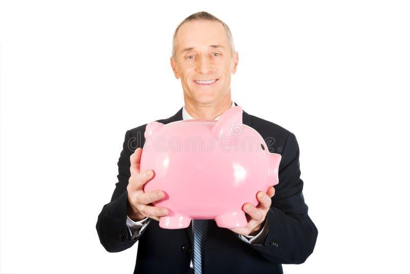 Stående av hållande piggybank för gladlynt affärsman arkivfoto