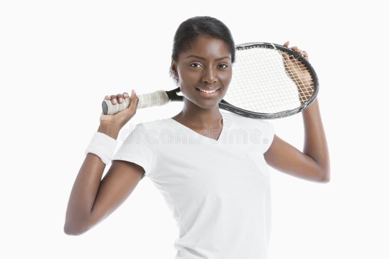 Stående av hållande racket för ung afrikansk amerikankvinna över vit bakgrund fotografering för bildbyråer