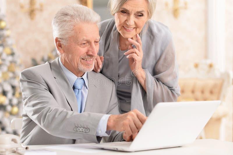 Stående av höga par genom att använda bärbara datorn hemma fotografering för bildbyråer