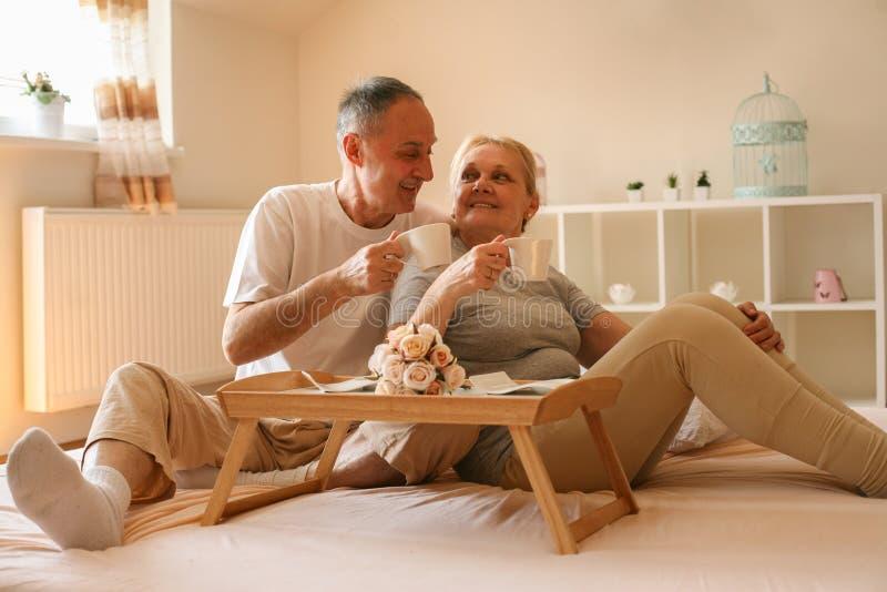 Stående av höga par som dricker kaffe i säng fotografering för bildbyråer