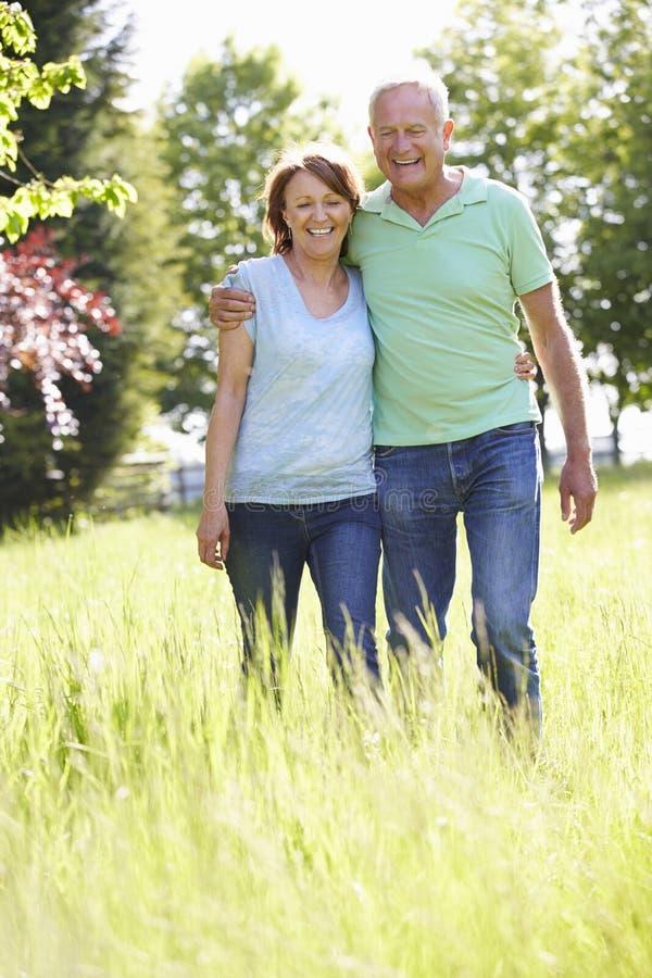 Stående av höga par som går i sommarbygd royaltyfri fotografi