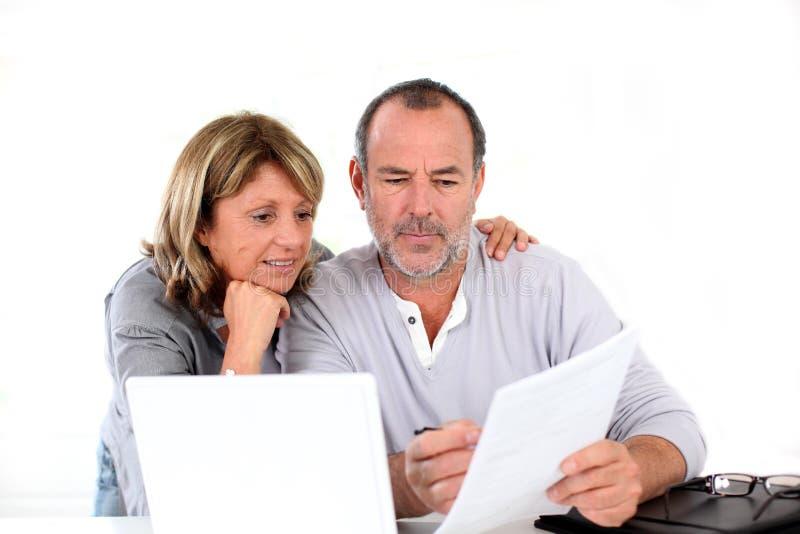 Stående av höga par som gör skrivbordsarbete arkivbilder