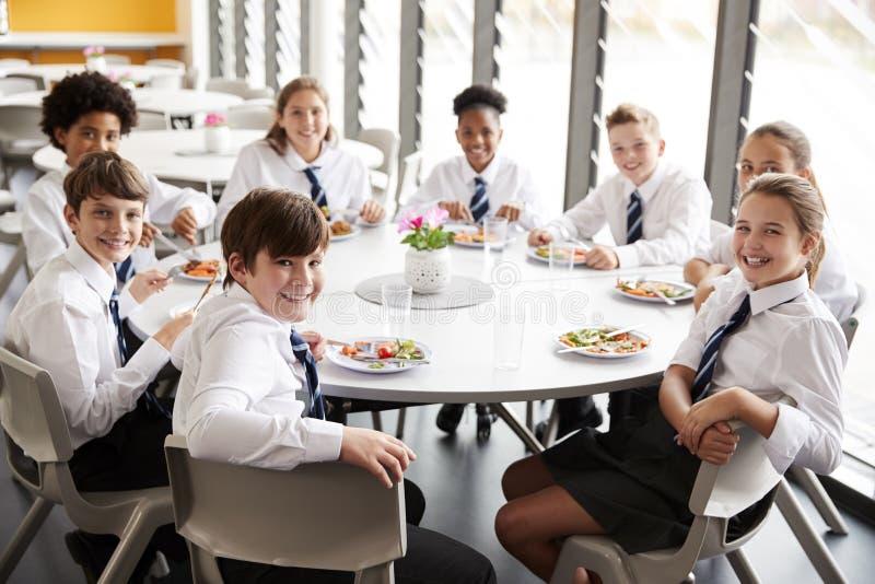 Stående av högstadiumstudenter som bär enhetligt sammanträde runt om tabellen och äter lunch i kafeteria royaltyfri bild