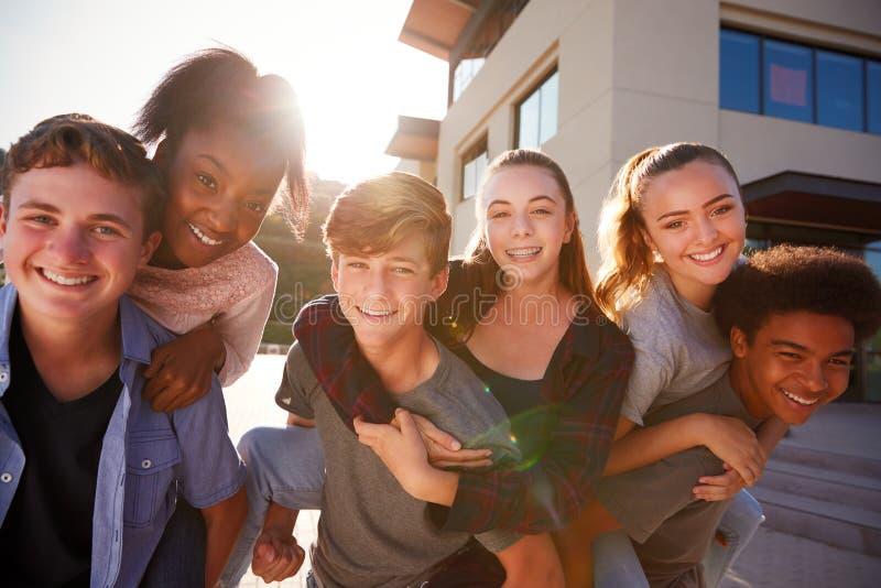 Stående av högstadiumstudenter som ger sig ridtur på axlarnahögskolabyggnader royaltyfri foto