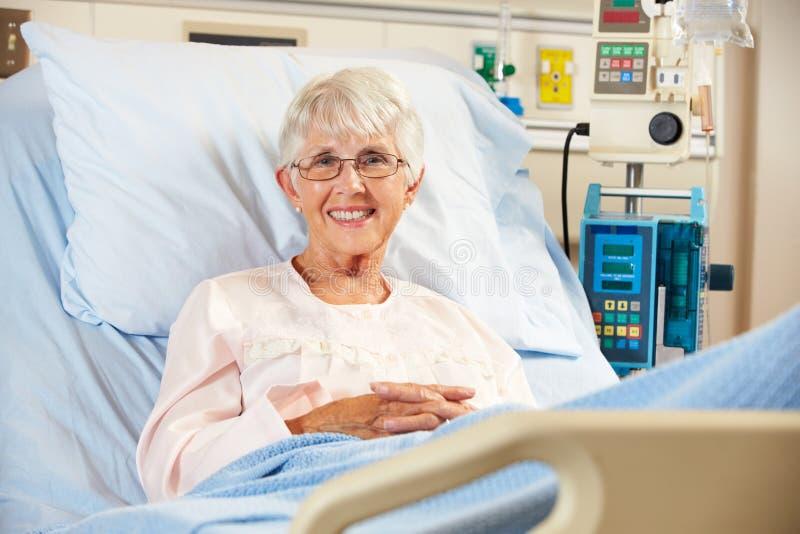 Stående av högt kvinnligt tålmodigt koppla av i sjukhussäng arkivbild