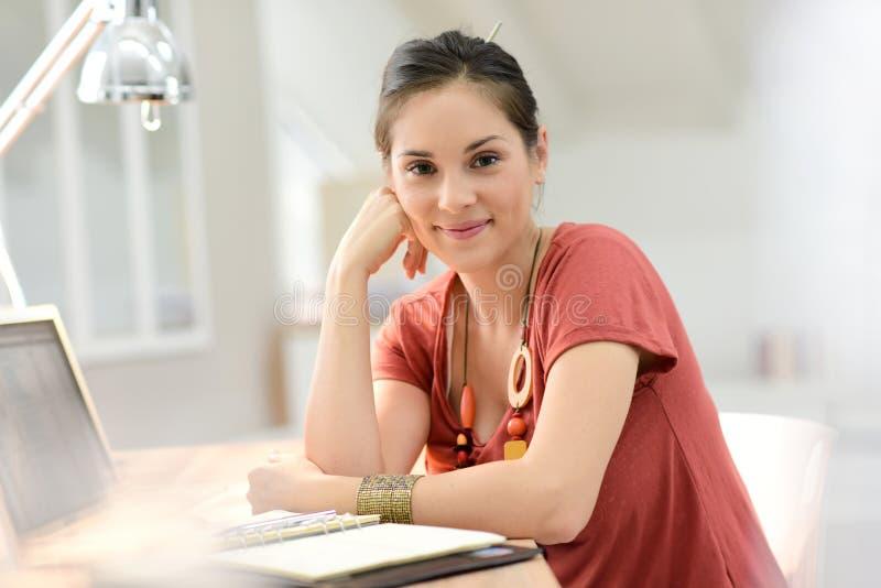 Stående av hemmastatt arbete för ung kvinna på bärbara datorn royaltyfri bild