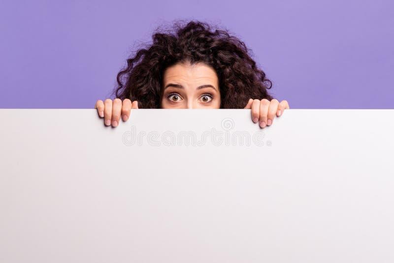 Stående av henne henne krabb-haired damvisning för trevlig attraktiv gladlynt häpen brunett som döljer bak plakat royaltyfria bilder