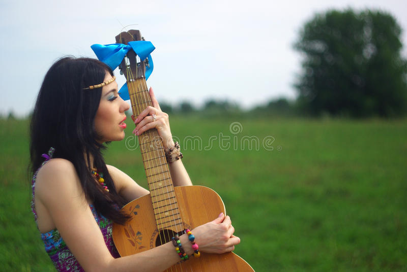 Stående av hippien som poserar som är utomhus- med gitarren fotografering för bildbyråer