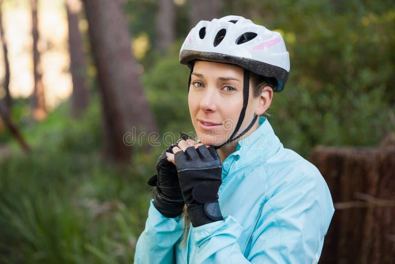 Stående av hjälmen för cykel för kvinnlig bergcyklist den bärande royaltyfria bilder