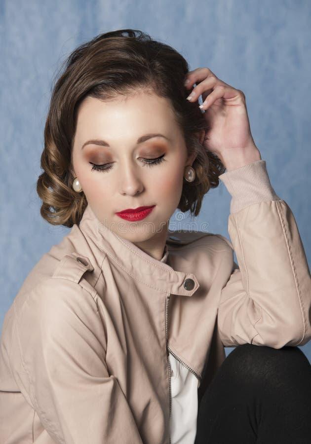 Stående av iklädda tappningkläder för härlig kvinna som bär en retro frisyr royaltyfri bild