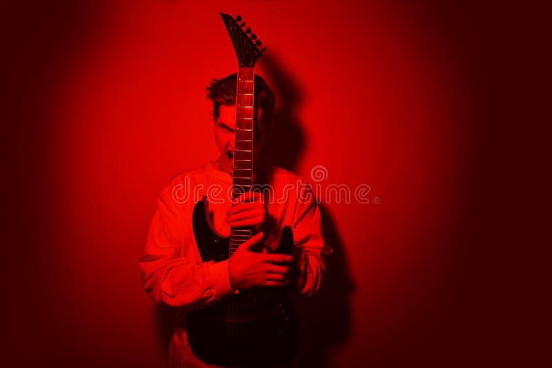 Stående av konstnären för ung man som skriker med hobbyen för elektrisk gitarr, musikbegrepp blom- vattenfärg för stjärna för roc arkivfoton