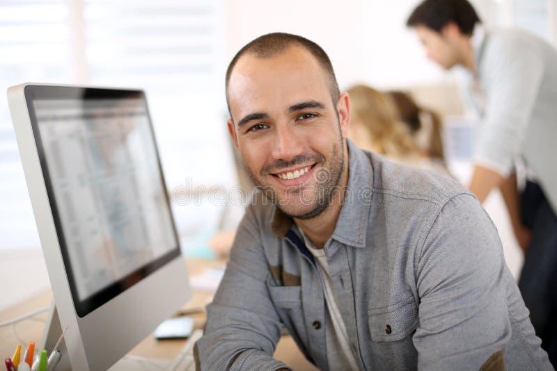 Stående av kontorsarbetaren för ung man i dator arkivfoto