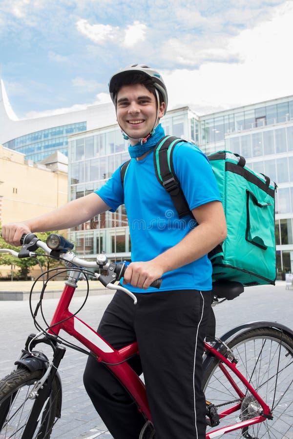 Stående av kurirOn Bicycle Delivering mat i stad royaltyfri bild