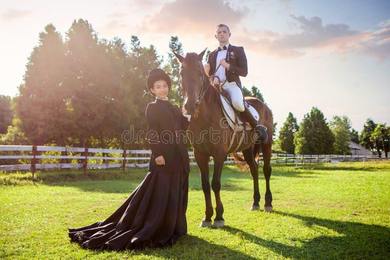 Download Stående Av Kvinnaanseendet Vid Mansammanträde På Häst På Fältet Under Solnedgång Arkivfoto - Bild av fält, häst: 78732410