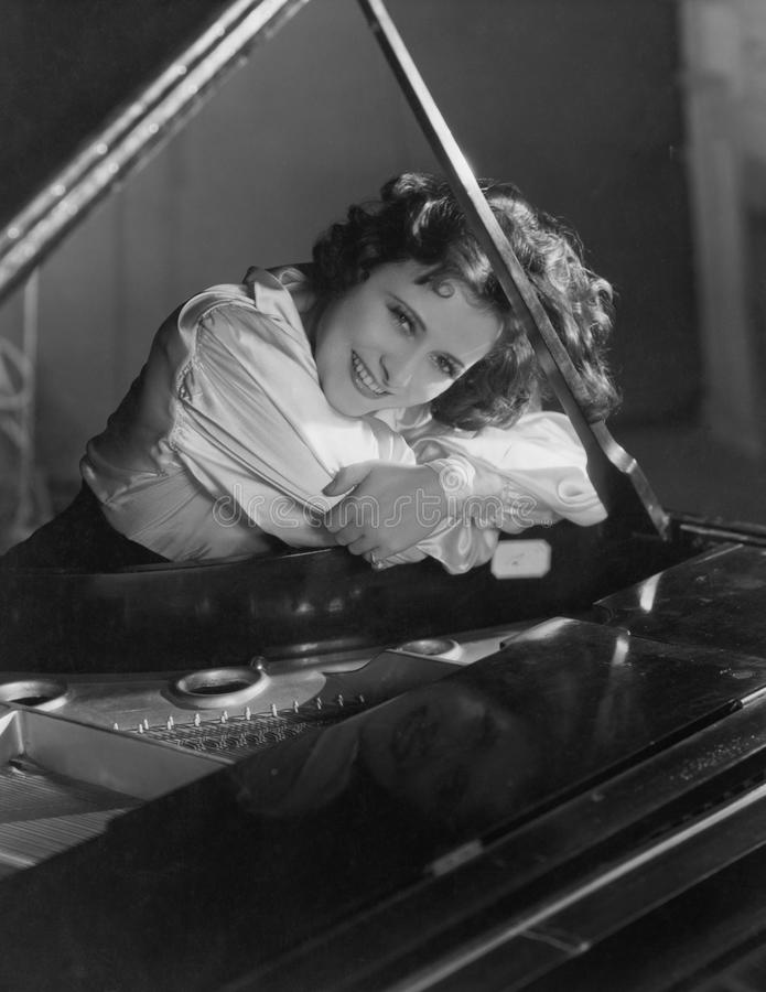 Stående av kvinnabenägenheten på piano (alla visade personer inte är längre uppehälle, och inget gods finns Leverantörgarantier s arkivfoto