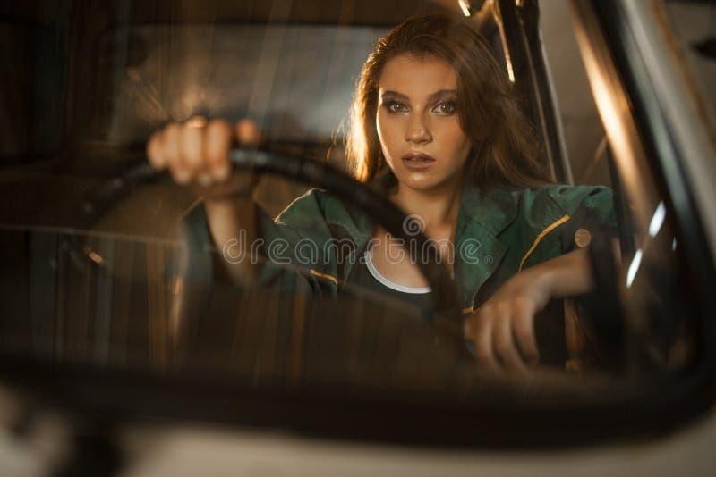 Stående av kvinnachauffören bak styrninghjulet av bilen Siktsthro arkivbild