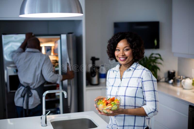 Stående av kvinnainnehavbunken av sallad medan man som öppnar ett kylskåp i bakgrund arkivfoto