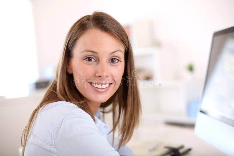 Stående av kvinnakontorsarbetaren framme av datoren royaltyfri bild