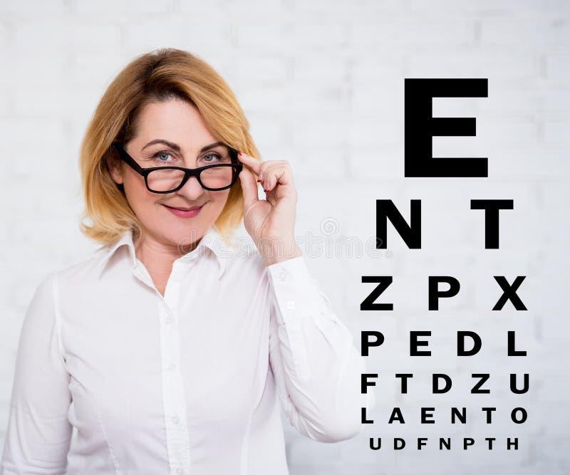 Stående av kvinnan för mogen affär i glasögon och eyevisionprovdiagrammet över den vita väggen royaltyfri bild