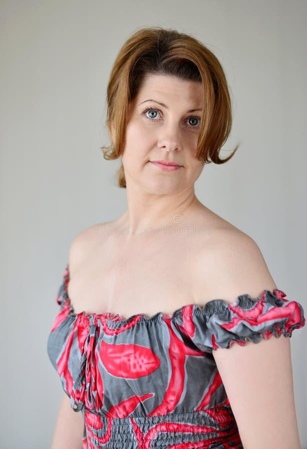 Stående av kvinnan i en klänning med kala skuldror arkivbild