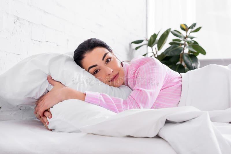 stående av kvinnan i rosa pyjamas som vilar i säng i morgon royaltyfria bilder