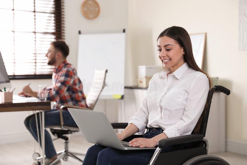 Stående av kvinnan i rullstol med bärbara datorn och hennes kollega arkivbilder