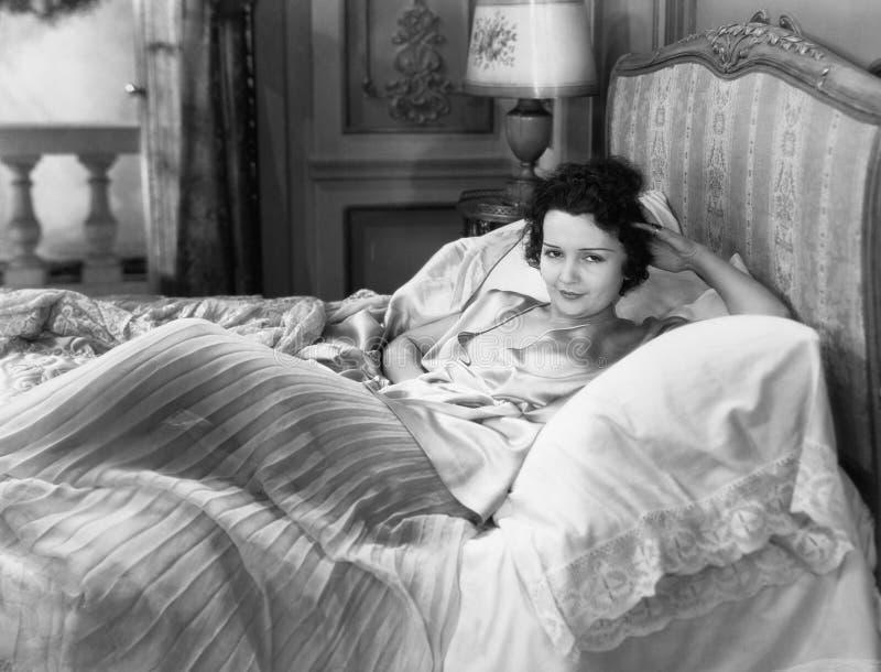 Stående av kvinnan i säng (alla visade personer inte är längre uppehälle, och inget gods finns Leverantörgarantier att det ska fi fotografering för bildbyråer