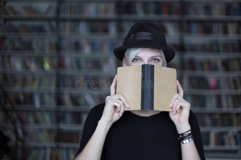 Stående av kvinnan i svart hatt med den öppnade boken, halva-täckt framsida, vitt hår Hipsterstudentflicka i ett arkiv royaltyfria foton