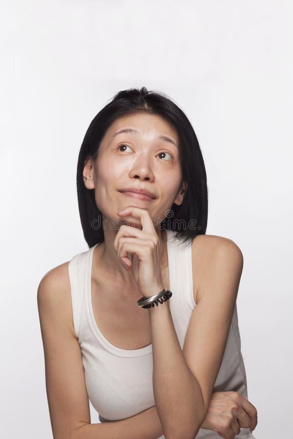 Stående av kvinnan med handen på hennes haka som ser upp i begrundande royaltyfria foton