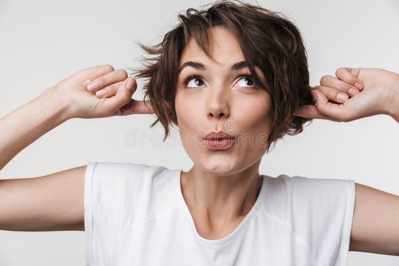 Stående av kvinnan med kort brunt hår i grundläggande t-skjorta som pluggar hennes öron med fingrar som isoleras över vit bakgrun royaltyfria bilder