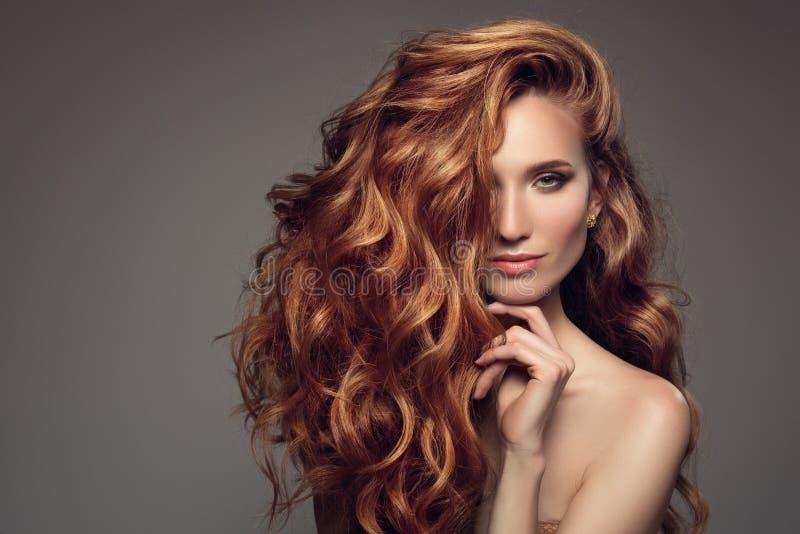 Stående av kvinnan med långt lockigt härligt ljust rödbrun hår royaltyfria bilder