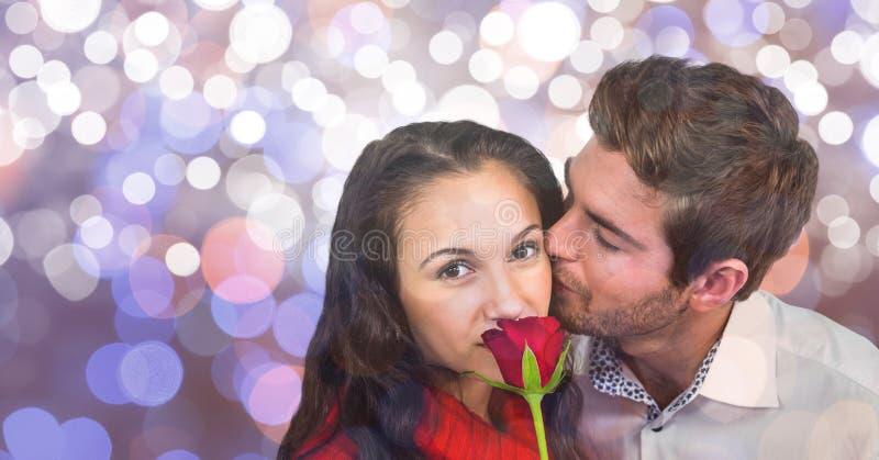 Stående av kvinnan med rosen som kyssas av mannen över bokeh royaltyfria foton