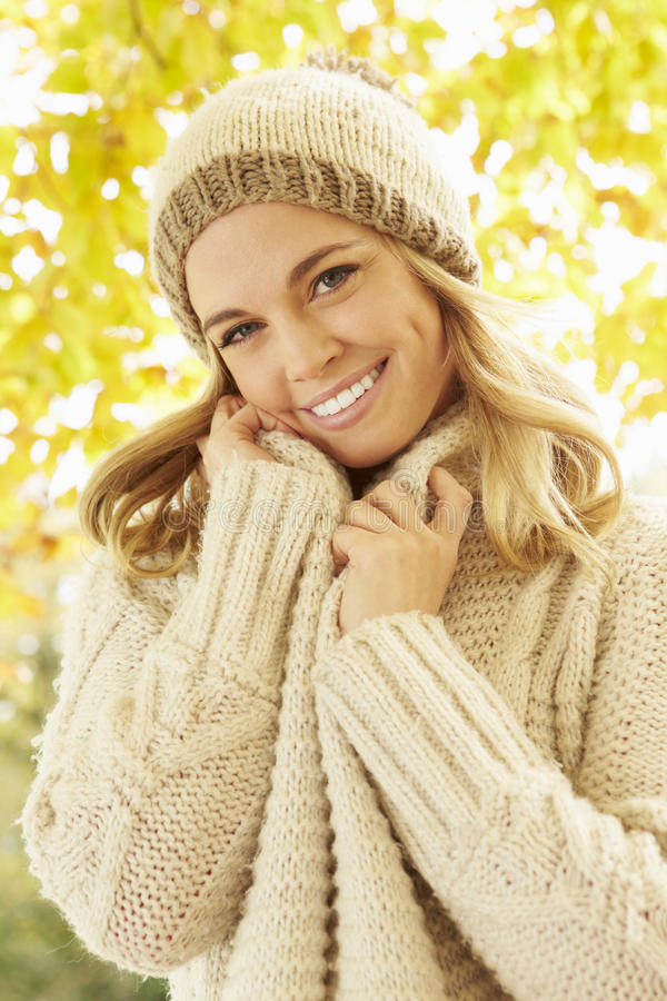 Stående av kvinnan som bär varm kläder under Autumn Tree arkivbild