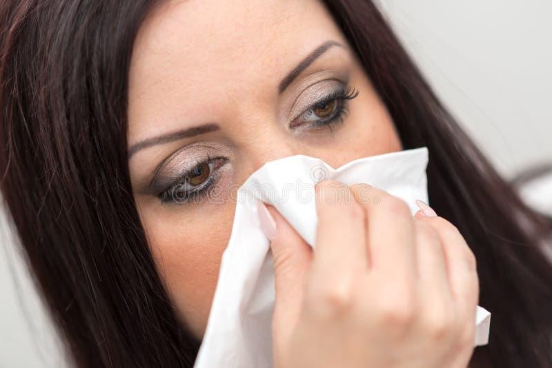 Stående av kvinnan som blåser upp hennes näsa, slut royaltyfri foto