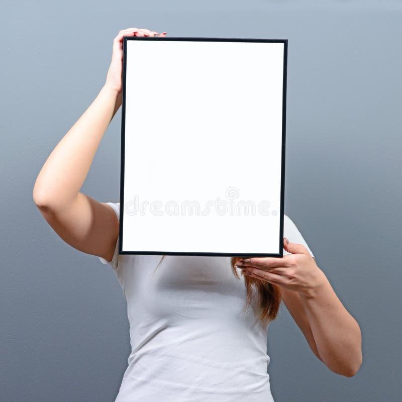 Stående av kvinnan som döljer bak tomt teckenbräde royaltyfria foton