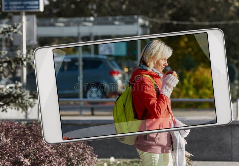 Stående av kvinnan som dricker kaffe på smartphonen arkivfoton