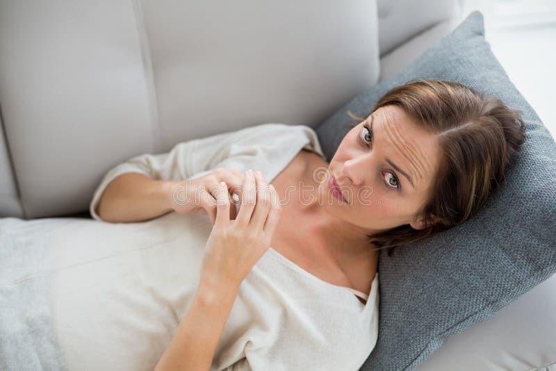 Stående av kvinnan som kopplar av på soffan arkivbild