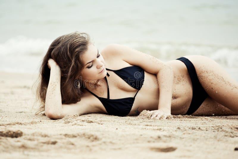 Stående av kvinnan som ligger på sandstranden royaltyfri foto
