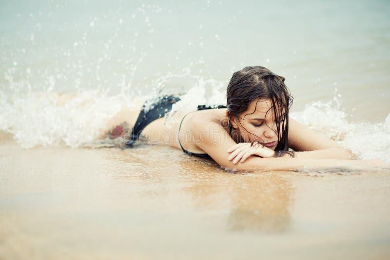 Stående av kvinnan som ligger på sandstranden arkivfoton