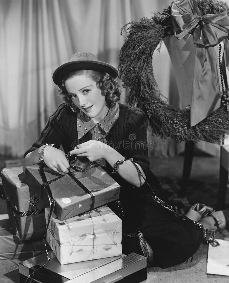 Stående av kvinnan som slår in julklappar (alla visade personer inte är längre uppehälle, och inget gods finns Leverantörwarranti arkivbild