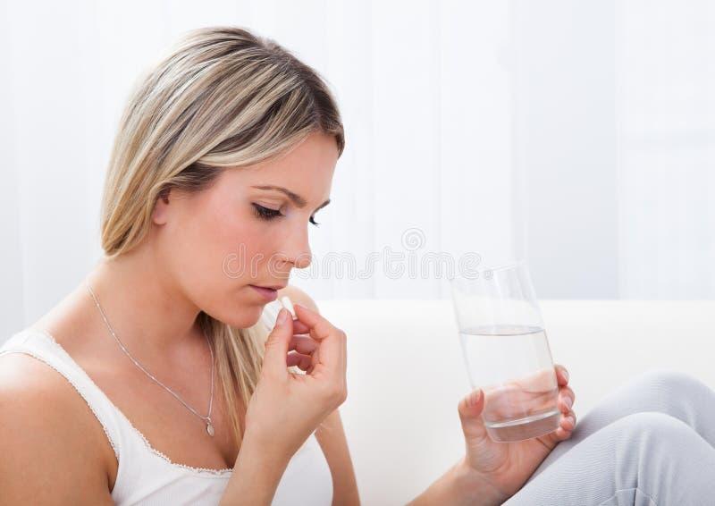 Stående av kvinnan som tar preventivpillerar royaltyfria bilder