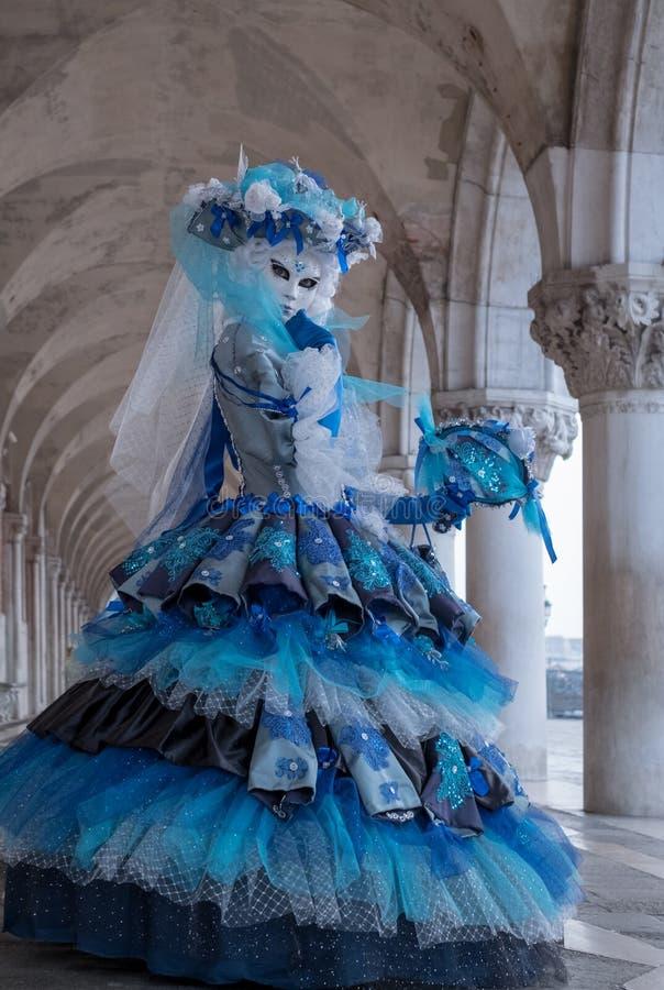 Stående av kvinnan som tillbaka ser över hennes skuldra, under bågarna på dogarna slott, Venedig, under karnevalet arkivfoton