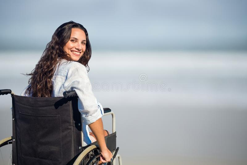 Stående av kvinnasammanträde på rullstolen på stranden fotografering för bildbyråer