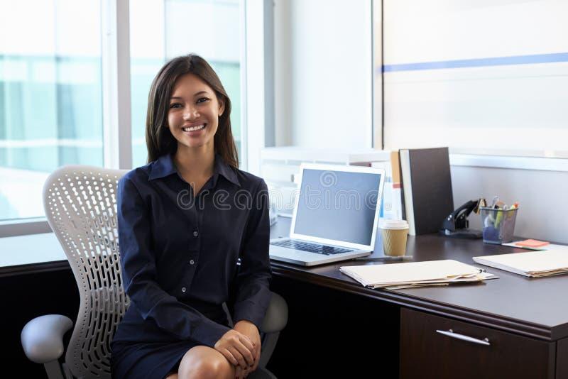 Stående av kvinnlig doktor Sitting At Desk i regeringsställning royaltyfri fotografi