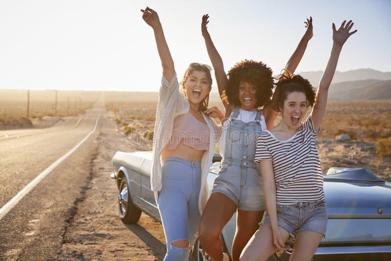 Stående av kvinnliga vänner som tycker om anseende för vägtur bredvid den klassiska bilen på ökenhuvudvägen arkivfoton